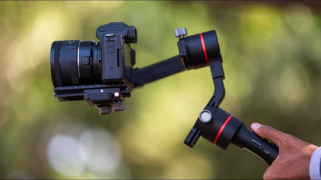 Hand holding a gimbal with a camera attached to it