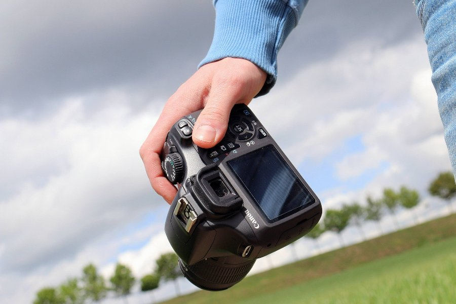 Person holding a dslr camera worth under 600 dollars
