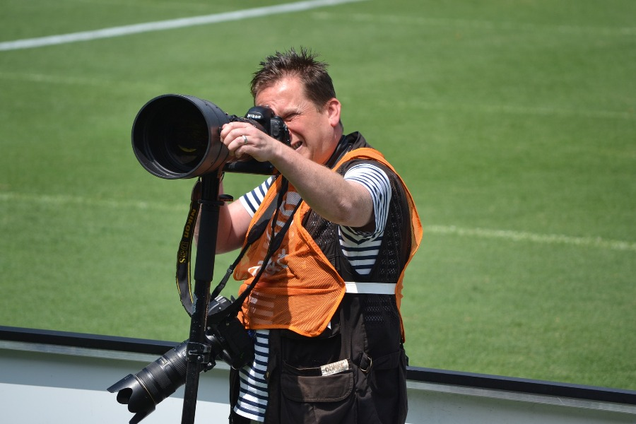 Sports photographer using a Nikon lens during an official game
