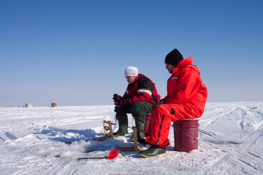 Men sitting in plastic containers and ice fishing