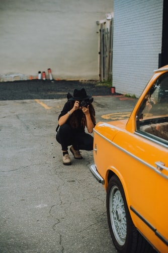 Woman photographing a car