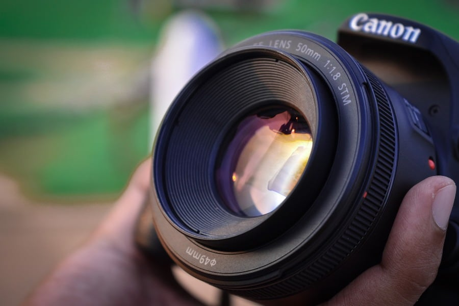 Person holding a 50mm camera lens