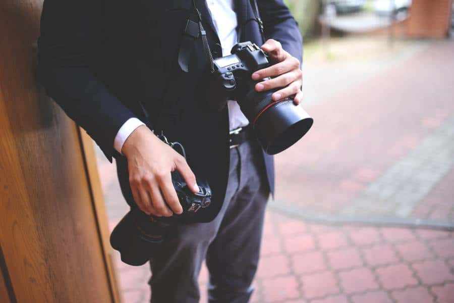 A wedding photographer carrying two cameras